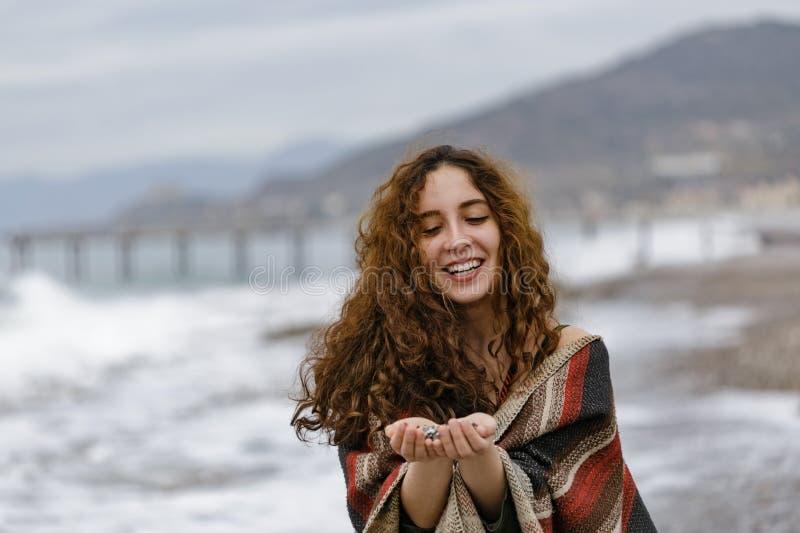 Mujer joven en el poncho rayado que sostiene los guijarros en sus palmas foto de archivo libre de regalías