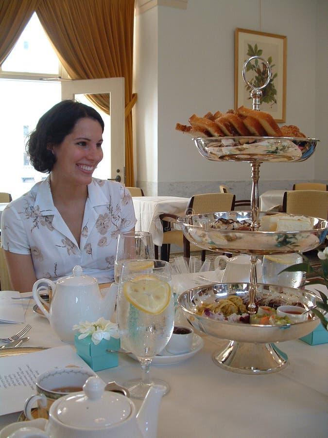 Mujer joven en el servicio de té apropiado imagen de archivo