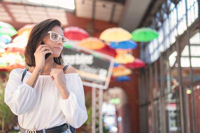 Mujer joven en el smartphone que mira al lado fotografía de archivo