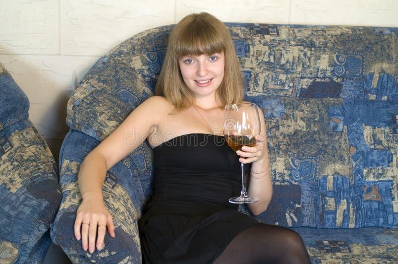 Mujer joven en el sofá imagenes de archivo