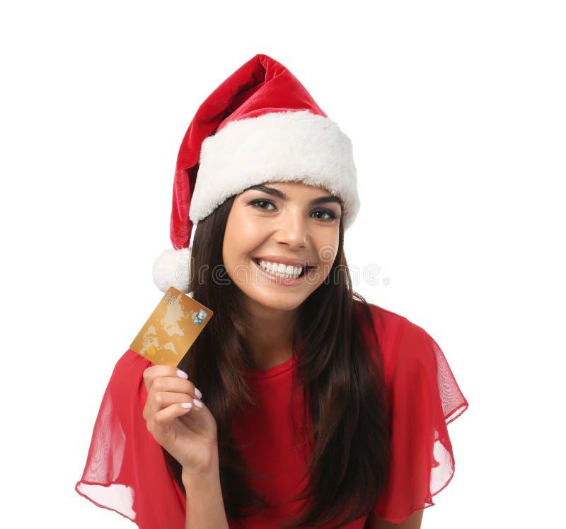 Mujer joven en el sombrero de Papá Noel con la tarjeta de crédito en el fondo blanco Compras en l?nea foto de archivo