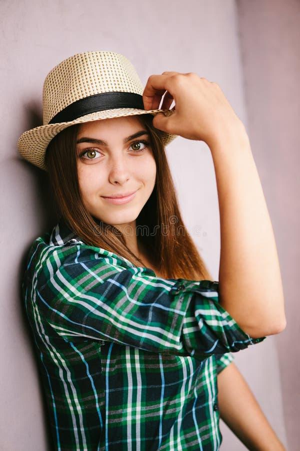 Mujer joven en el sombrero que mira en la cámara y la sonrisa foto de archivo