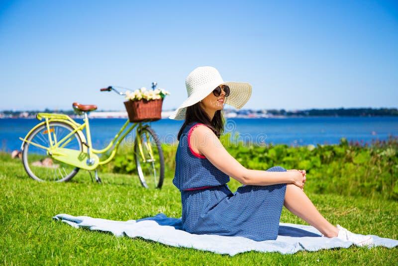 Mujer joven en el sombrero que se sienta en la costa de mar con la bicicleta del vintage fotografía de archivo