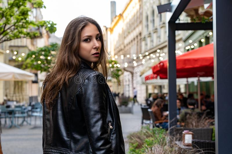 Mujer joven en el soporte negro de la chaqueta de cuero medio una vuelta en la calle de la ciudad de Lviv Fotografía de la moda d foto de archivo