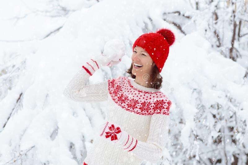 Mujer joven en el suéter hecho punto que juega lucha de la bola de la nieve en invierno Muchacha en juego de bolas de la nieve de fotografía de archivo
