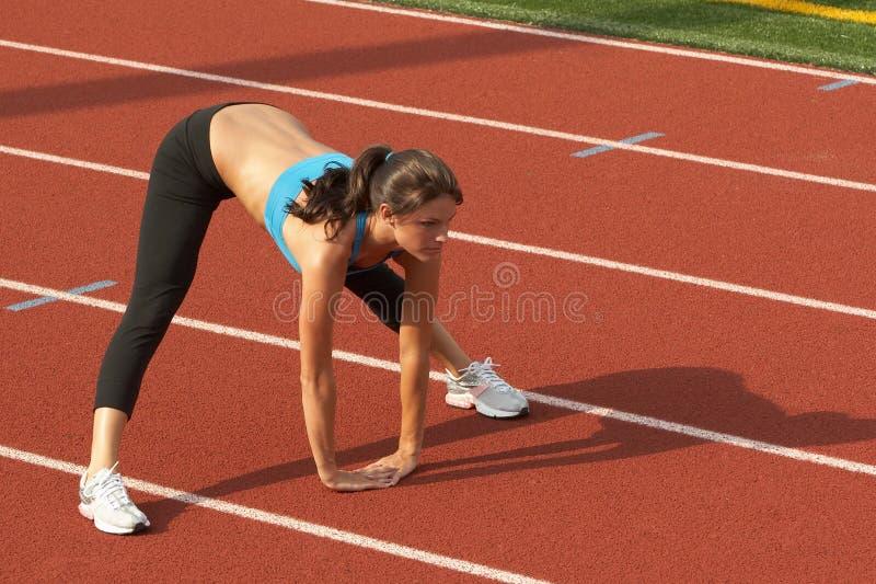 Mujer joven en el sujetador de los deportes que se inclina adelante y que estira los tendones de la corva foto de archivo libre de regalías