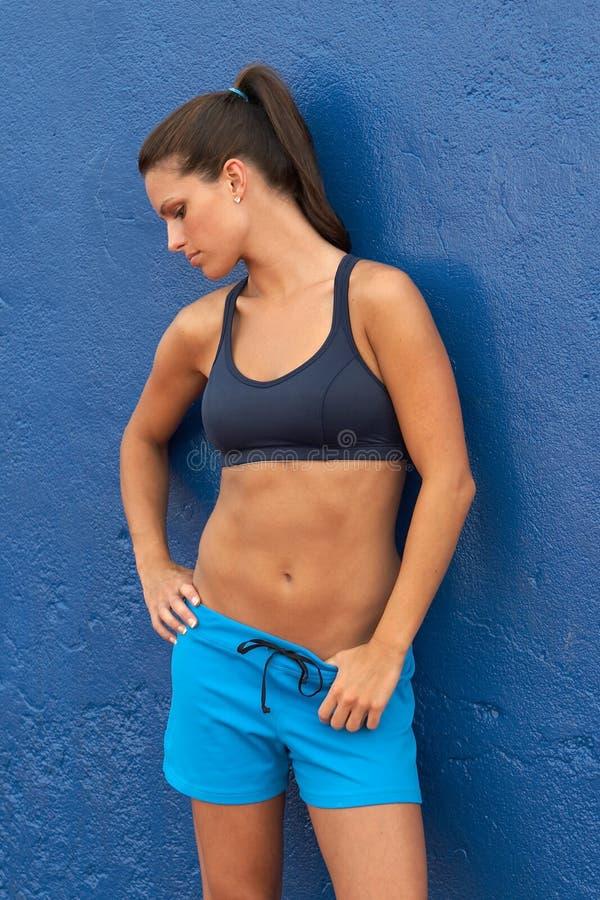 Mujer joven en el sujetador de los deportes que se inclina en la pared azul imagenes de archivo