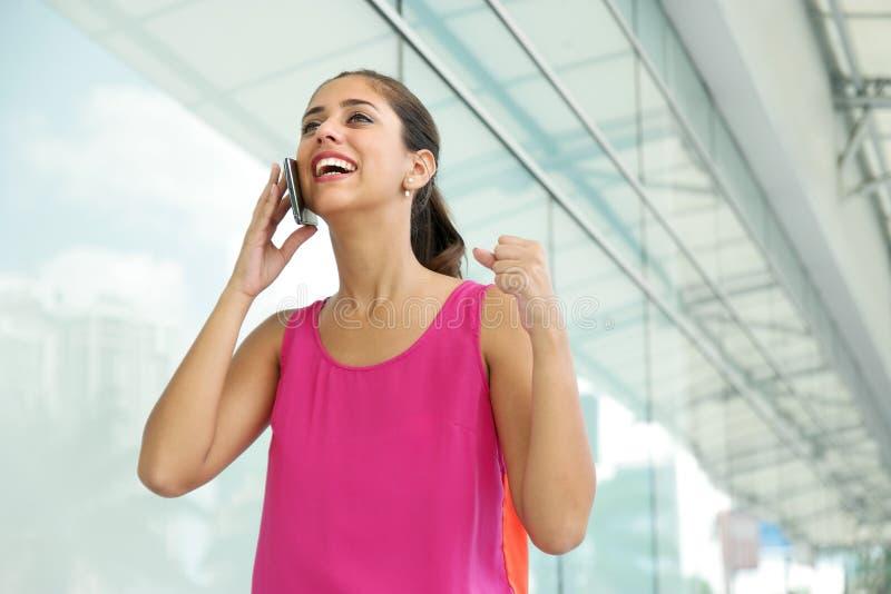 Mujer joven en el teléfono que sonríe para la alegría imagenes de archivo