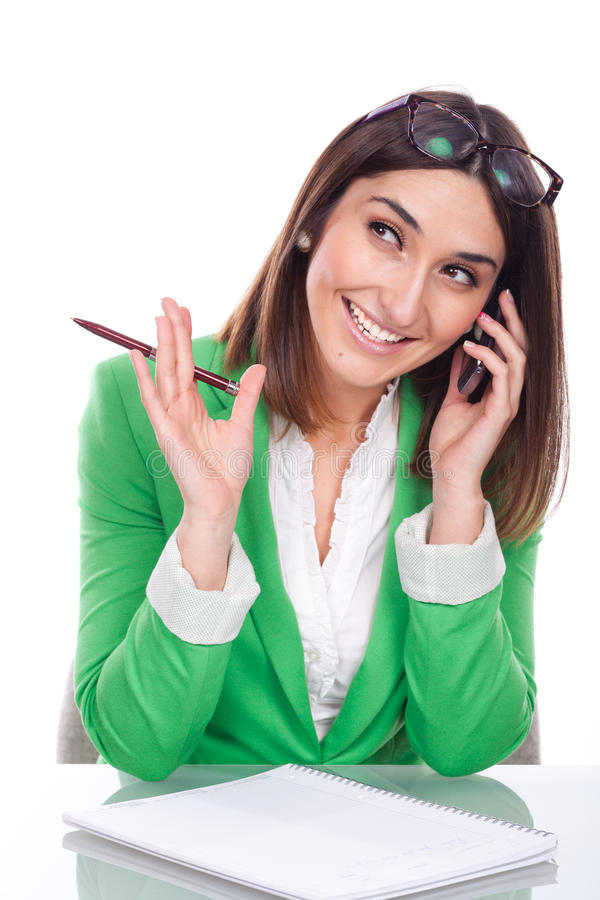 Mujer joven en el trabajo que sonríe a su móvil foto de archivo libre de regalías