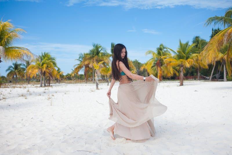 Mujer joven en el traje de baño y la falda que fluye, bailando en una playa del Caribe imagenes de archivo