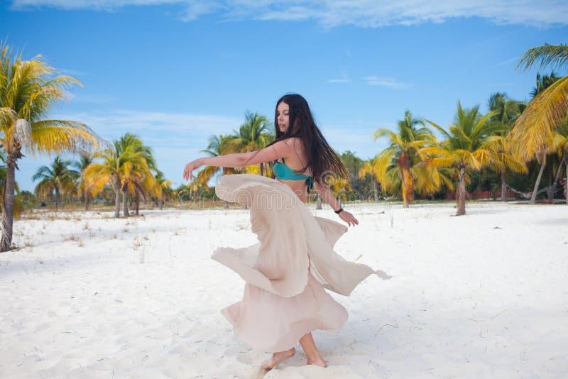 Mujer joven en el traje de baño y la falda que fluye, bailando en una playa del Caribe imagen de archivo