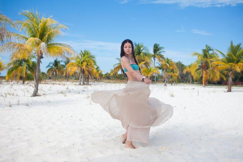 Mujer joven en el traje de baño y la falda que fluye, bailando en una playa del Caribe fotografía de archivo