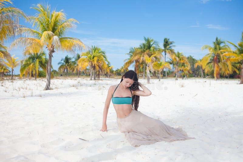 Mujer joven en el traje de baño y la falda que fluye, bailando en una playa del Caribe foto de archivo libre de regalías
