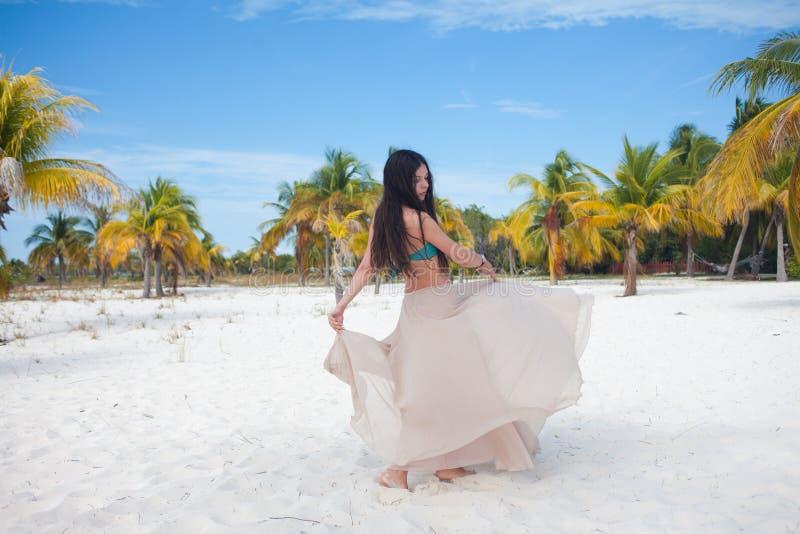 Mujer joven en el traje de baño y la falda que fluye, bailando en una playa del Caribe foto de archivo