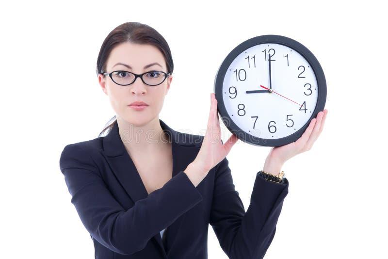 Mujer joven en el traje de negocios que sostiene el reloj de la oficina aislado en wh imagen de archivo