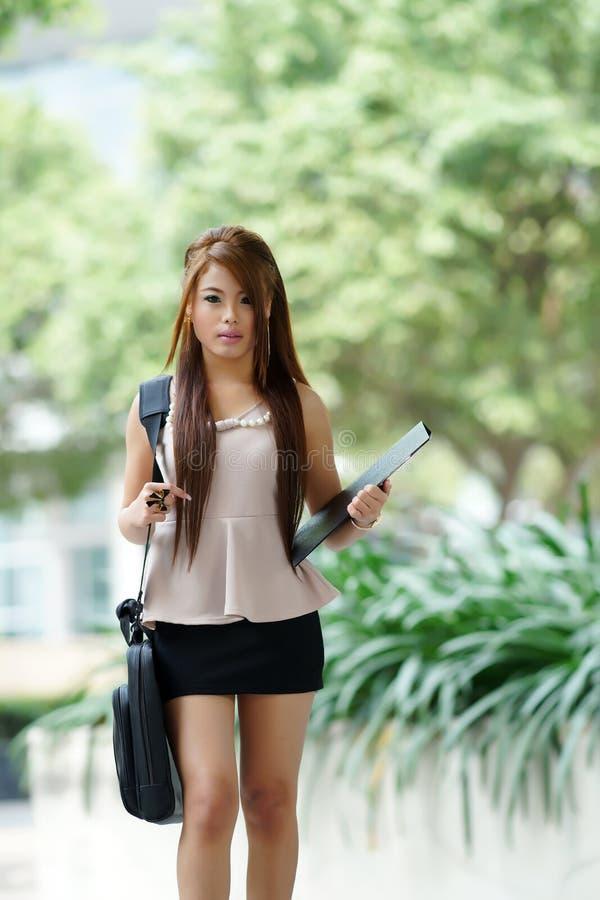 Mujer joven en el traje del asunto, cartera que lleva y f el sostenerse fotos de archivo