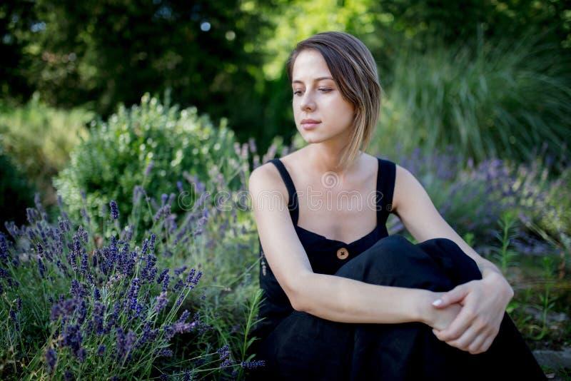 Mujer joven en el vestido oscuro que se sienta cerca de las flores de la lavanda foto de archivo libre de regalías