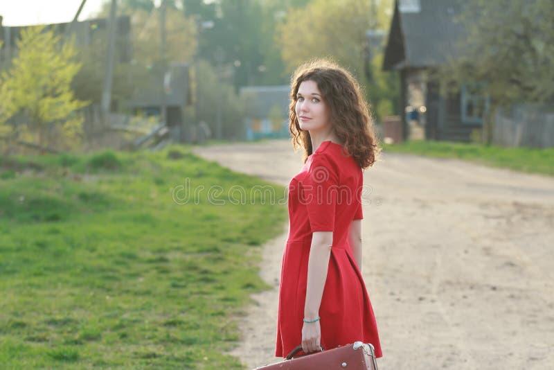 Mujer joven en el vestido rojo femenino que mira sobre su hombro durante su viaje del vintage foto de archivo libre de regalías
