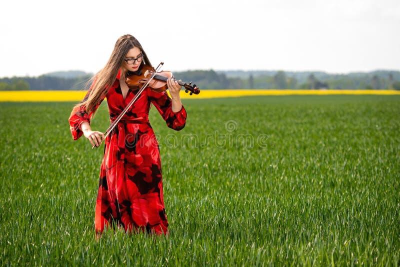 Mujer joven en el vestido rojo que toca el violín en el prado verde - imagen fotografía de archivo libre de regalías
