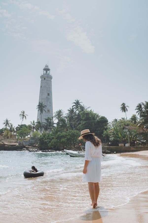 Mujer joven en el vestido y el sombrero blancos que camina a lo largo de la playa contra el faro imágenes de archivo libres de regalías