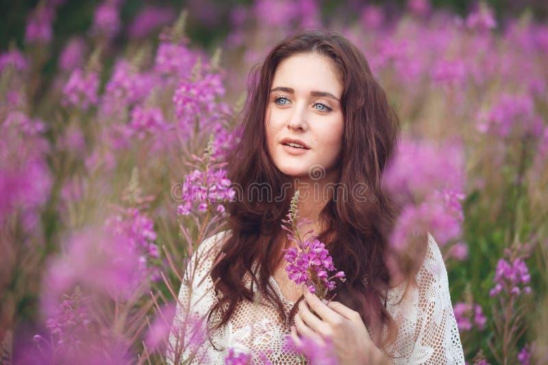 Mujer joven en flores rosadas fotografía de archivo