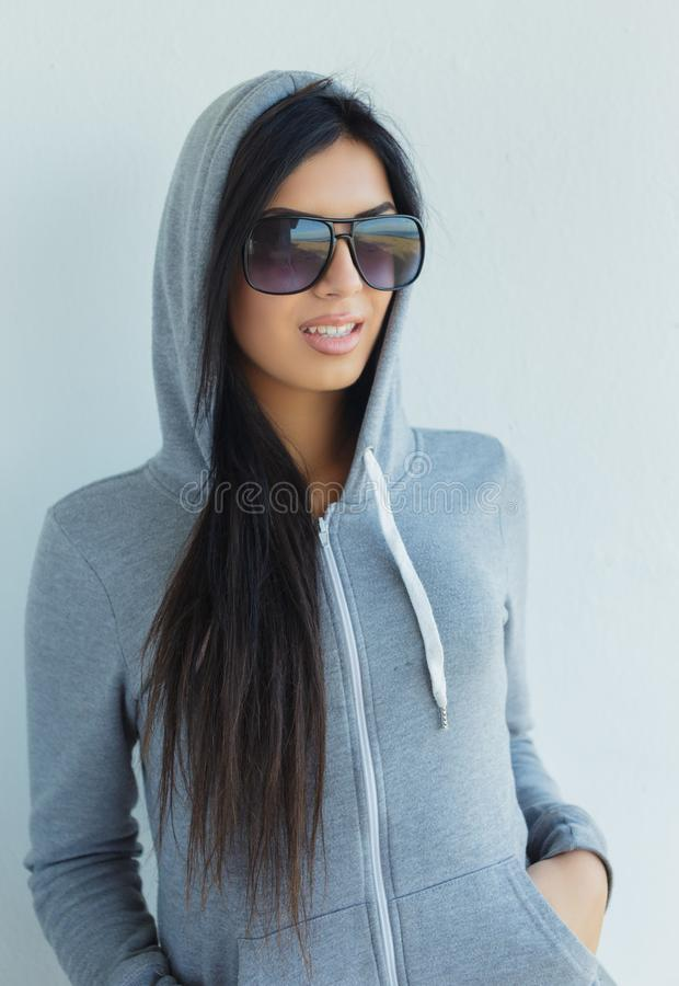 Mujer joven en gafas de sol y sudadera con capucha gris foto de archivo