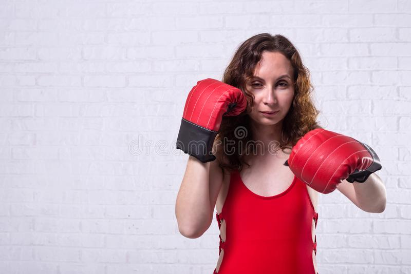 Mujer joven en guantes de boxeo rojos en un fondo blanco del ladrillo foto de archivo libre de regalías