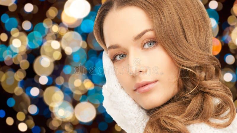 Mujer joven en guantes sobre luces de la Navidad imagen de archivo libre de regalías
