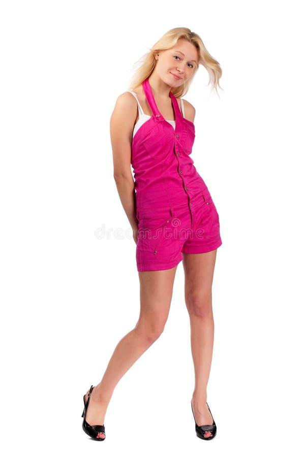 Mujer joven en guardapolvos rosados cortos fotos de archivo