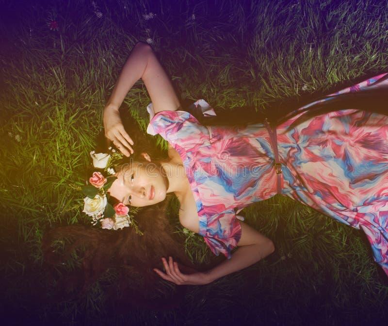 mujer joven en guirnalda de folwers en una hierba verde fotografía de archivo