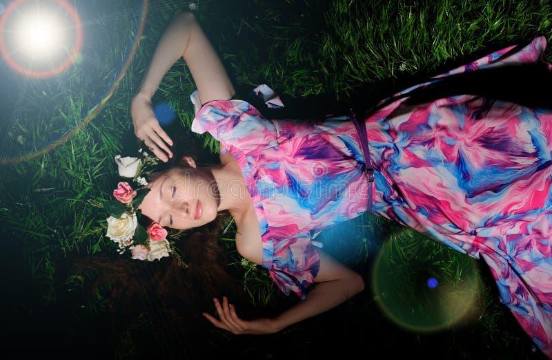 mujer joven en guirnalda de folwers en una hierba verde imágenes de archivo libres de regalías