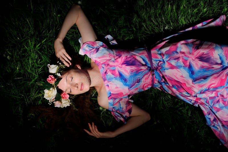 mujer joven en guirnalda de folwers en una hierba verde imagenes de archivo