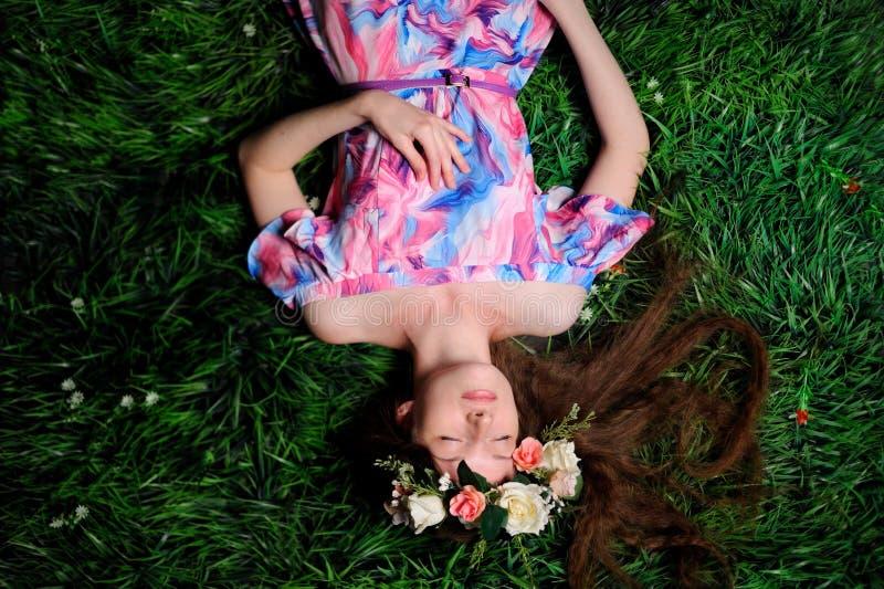 mujer joven en guirnalda de folwers en una hierba verde foto de archivo