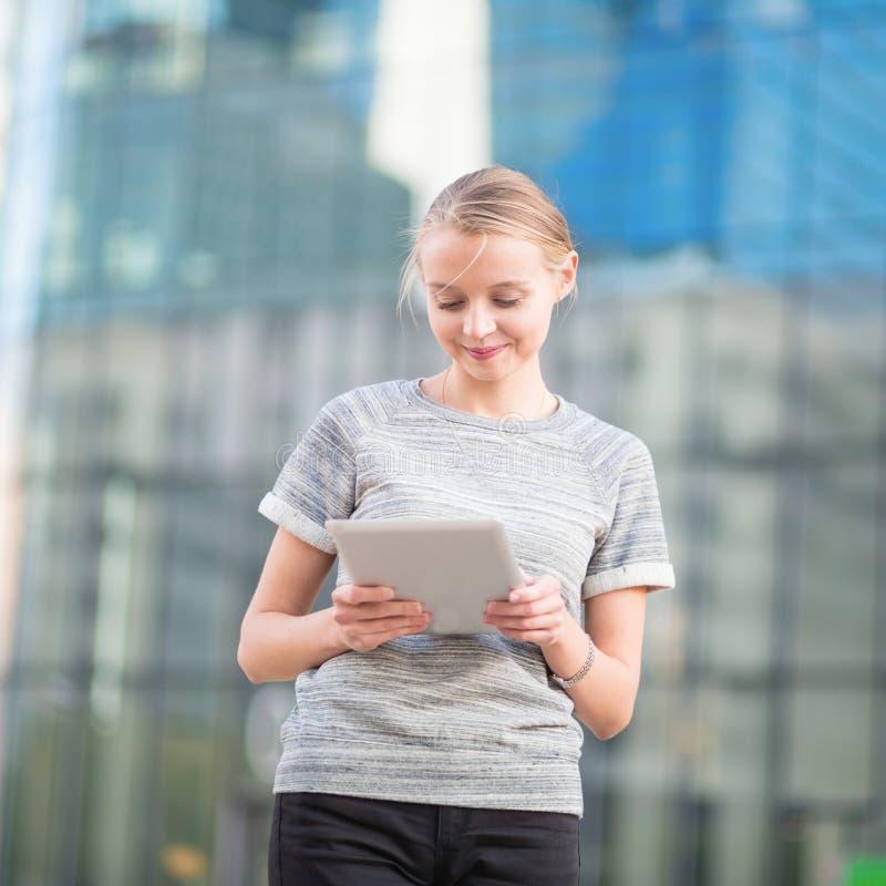 Mujer joven en interior de la oficina usando la tableta imagen de archivo