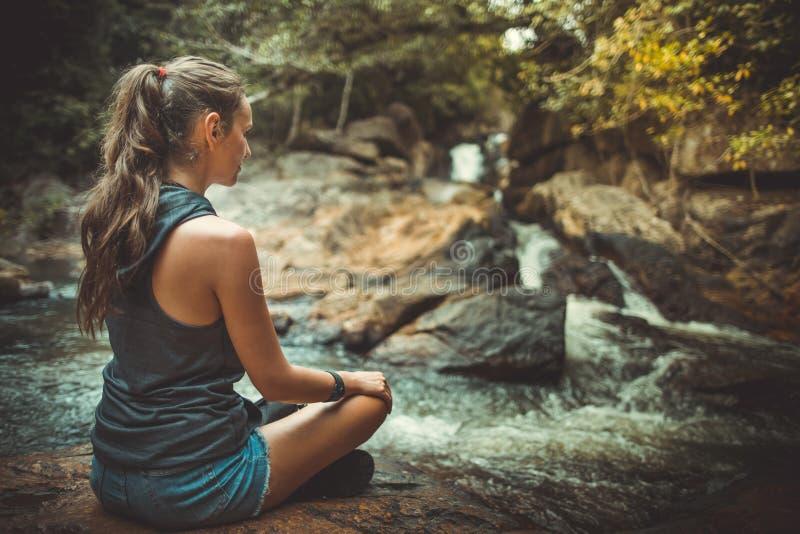 Mujer joven en la actitud de la yoga que se sienta cerca de la cascada fotografía de archivo libre de regalías