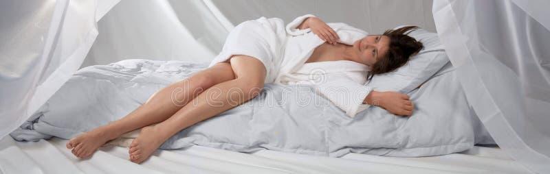 Mujer joven en la albornoz blanca en la cama blanca fotografía de archivo libre de regalías