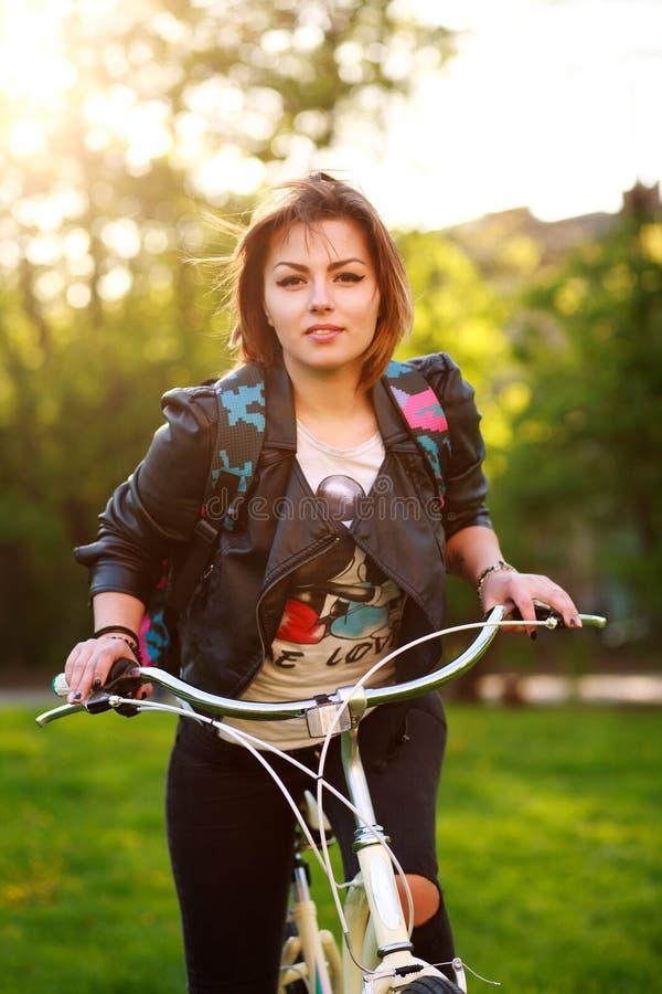 Mujer joven en la bicicleta en parque verde en puesta del sol fotos de archivo libres de regalías