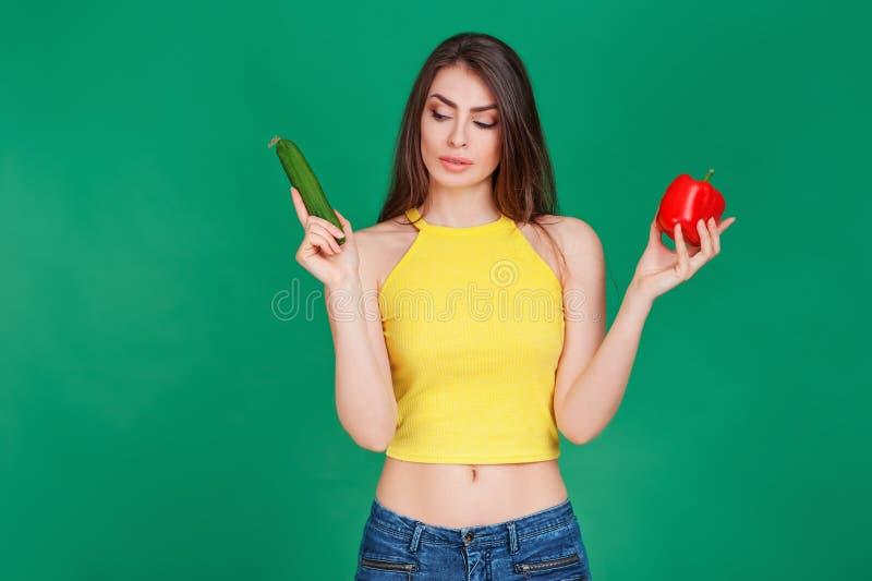 Mujer joven en la buena forma que sostiene el pepino verde y la pimienta roja de la ensalada en manos y que piensa en la opción D foto de archivo