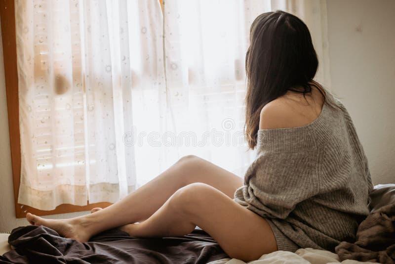 Mujer joven en la cama que mira a través de la ventana con un suéter y piernas desnudas imágenes de archivo libres de regalías