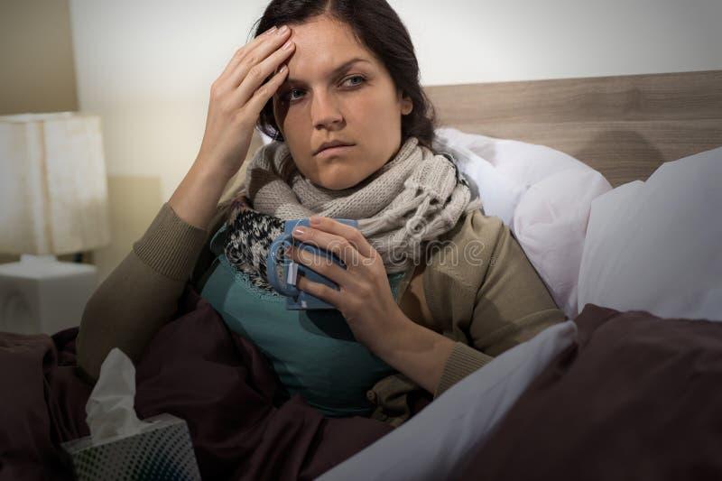 Mujer joven en la cama que tiene gripe imagen de archivo