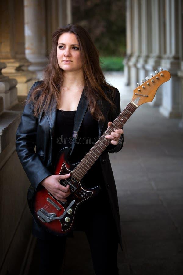 Mujer joven en la chaqueta de cuero negra que toca la guitarra al aire libre fotografía de archivo libre de regalías