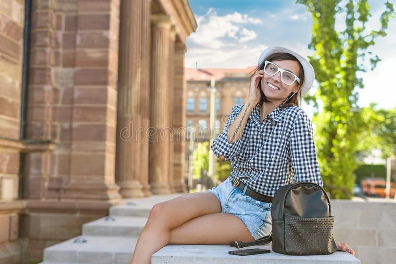 Mujer joven en la ciudad, muchacha de moda del inconformista de la sonrisa fotografía de archivo