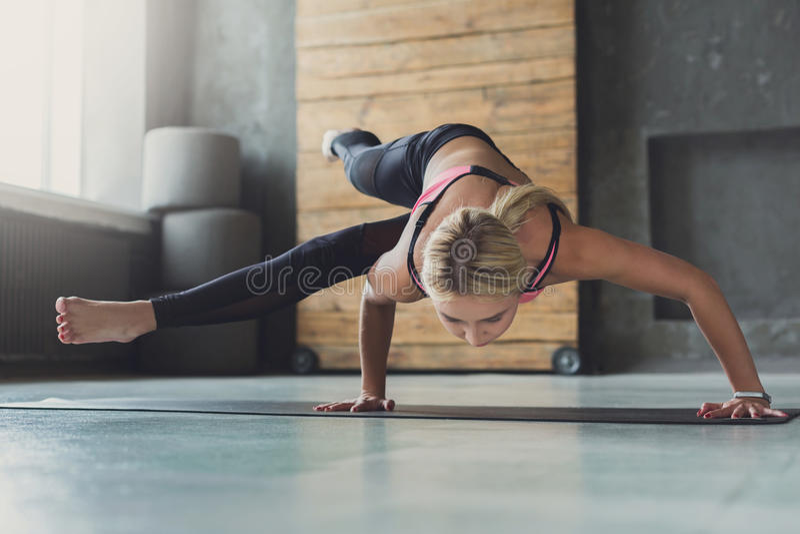 Mujer joven en la clase de la yoga, asana de la actitud del Ocho-ángulo imagenes de archivo