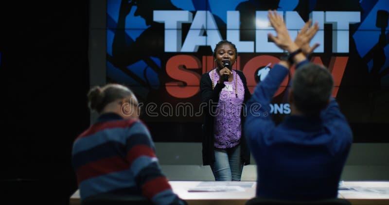 Mujer joven en la competencia del canto imagen de archivo