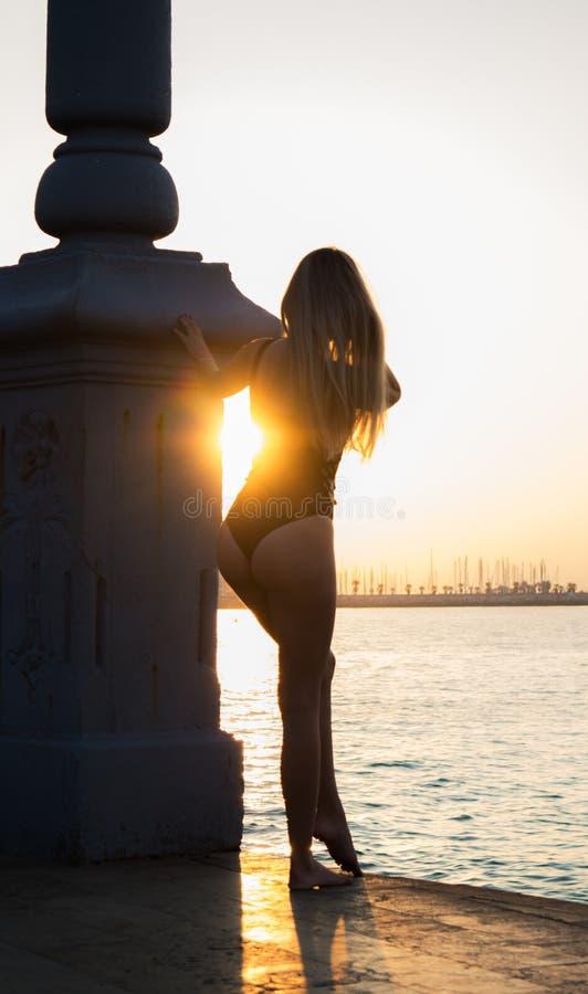 Mujer joven en la costa en la puesta del sol imagenes de archivo