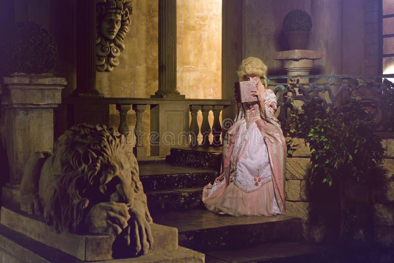 Mujer joven en la imagen del siglo XVIII que presenta en exterior del vintage imagenes de archivo