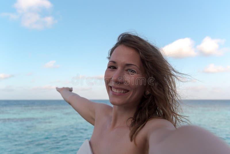 Mujer joven en la luna de miel que toma un selfie Mar como fondo fotos de archivo