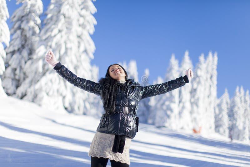 Mujer joven en la montaña en el invierno imagenes de archivo