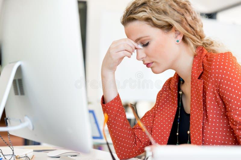 Mujer joven en la oficina cansada imagenes de archivo