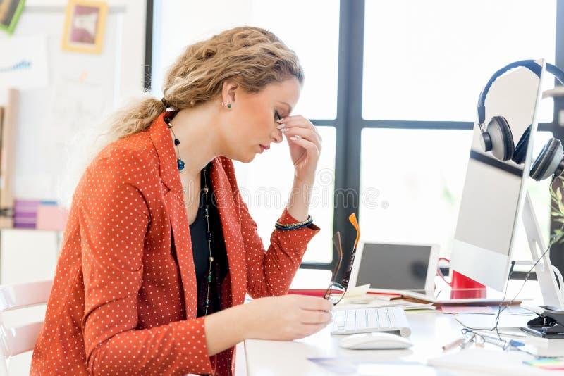 Mujer joven en la oficina cansada fotografía de archivo